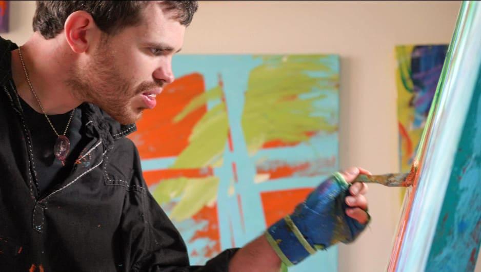 Homem branco com deficiência pintando um quadro. Descrição detalhada na legenda abaixo.