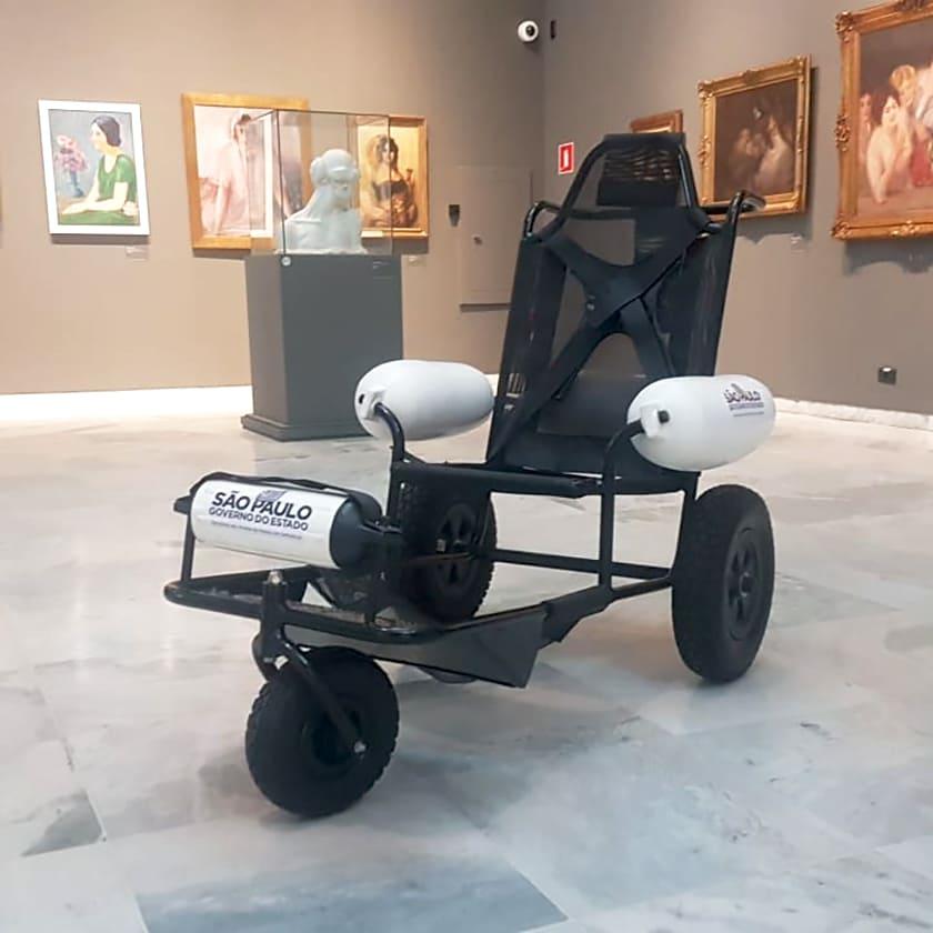 Foto de cadeira anfíbia para levar pessoas com deficiência ao mar e trilhas planas.