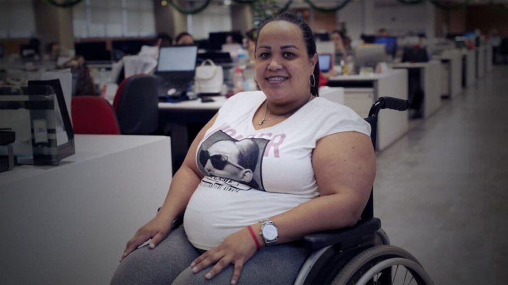 Foto de Gabriela Peña, mulher em cadeira de rodas, em ambiente corporativo. Descrição detalhada na legenda.