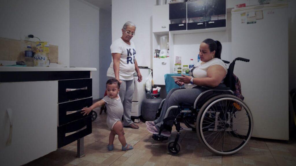 A venezuelana Gabriela Peña, mulher em cadeira de rodas, em frente da filha de 1 anoi, segurando a mão da avó.
