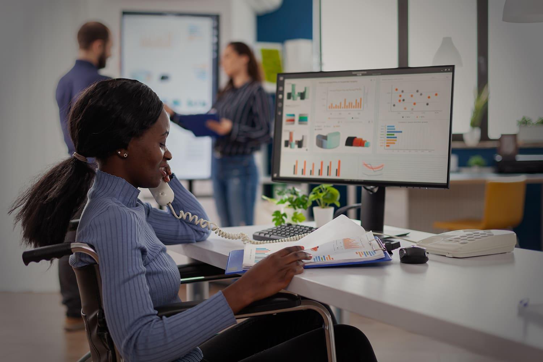 """Mulher negra em cadeira de rodas, no escritório, ilustrando a pauta """"Contratar PcDs gera benefícios às empresas e fomenta o ecossistema da inclusão""""."""