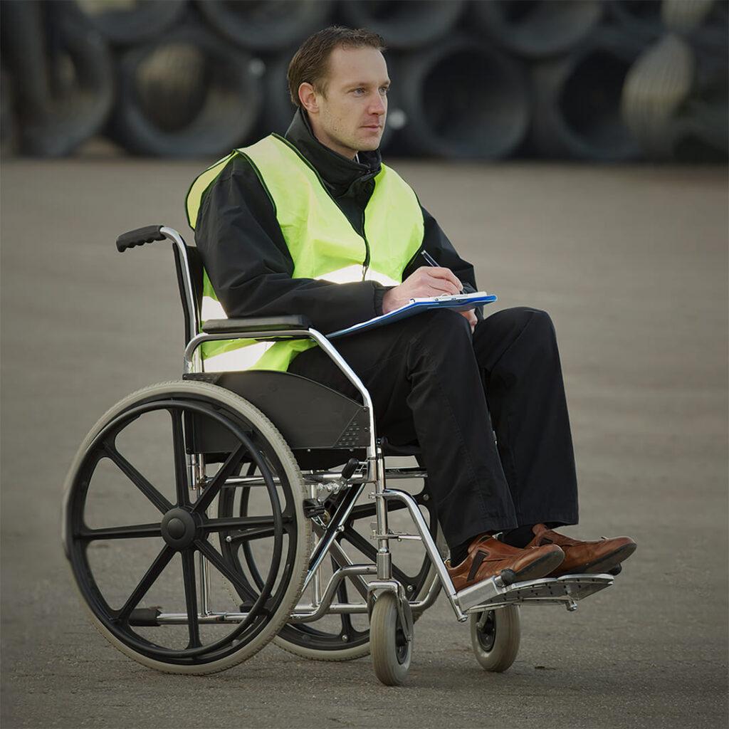 Homem branco em cadeira de rodas, com colete de identificação.