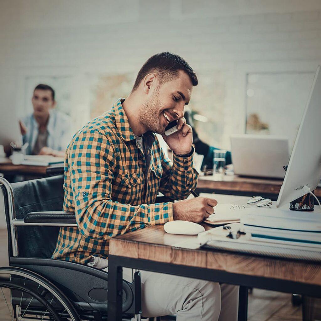 Homem moreno em cadeira de rodas falando no telefone.