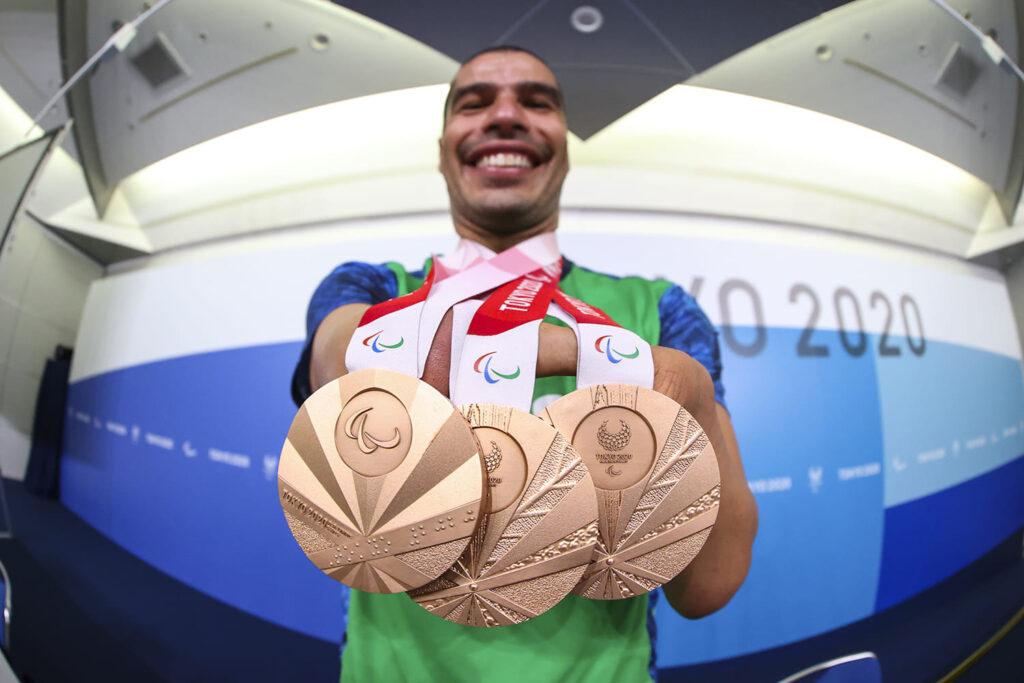 Fotografia do atleta Daniel Dias exibindo três medalhas de bronze penduradas no pescoço.