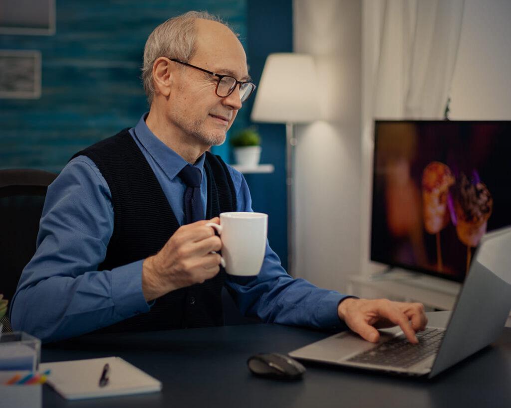 Homem idoso, de pele branca e cabelos grisalhos, trabalhando com o computador laptop e uma xícara branca na mão. Ilustra 5 motivos para contratar um idoso.