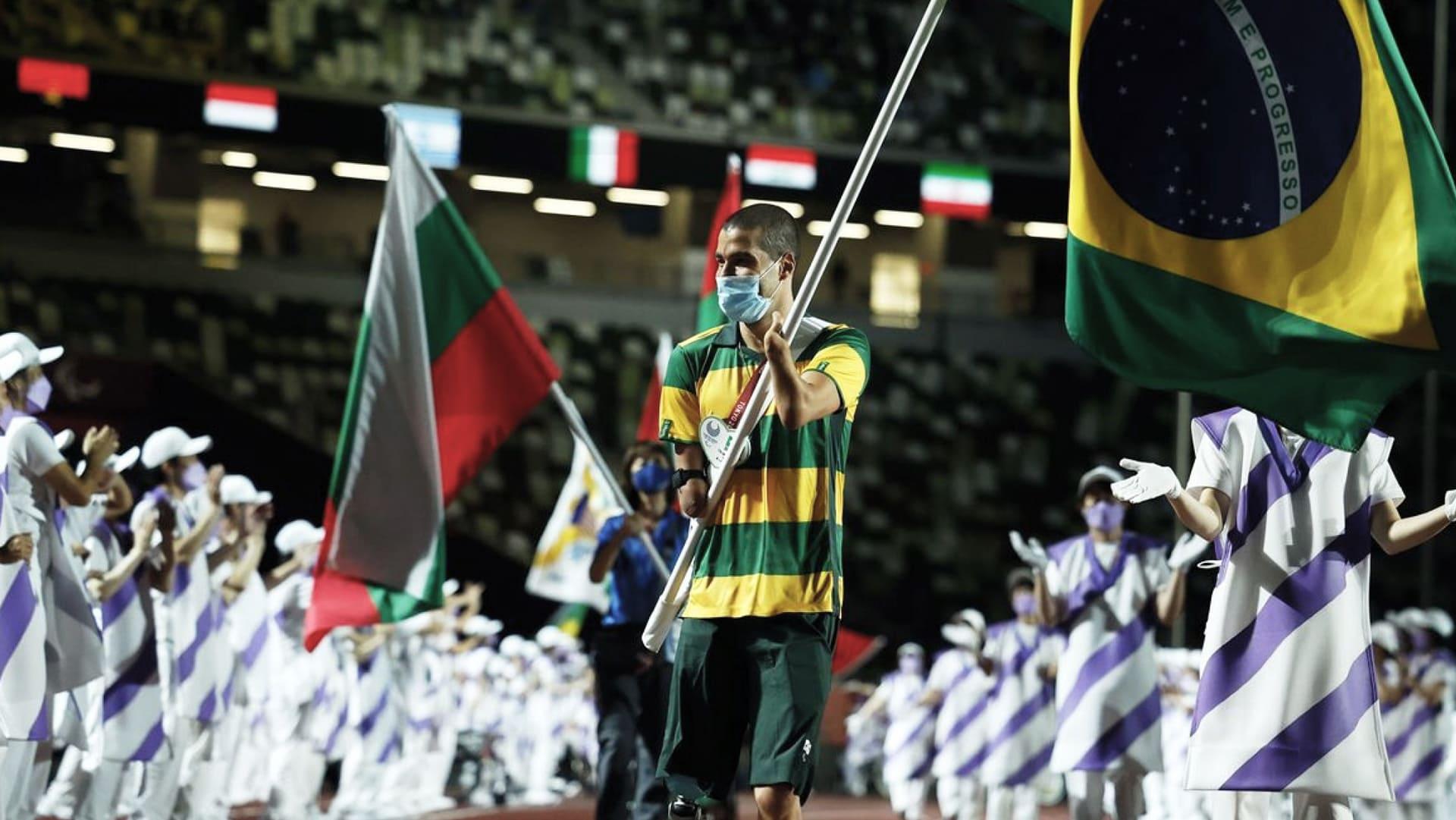 Fotografia do medalhista Daniel Dias, na cerimônia de encerramento da Paralimpíada no Japão, em Tóquio, dia 5 de setembro. Daniel carrega a bandeira do Brasil.