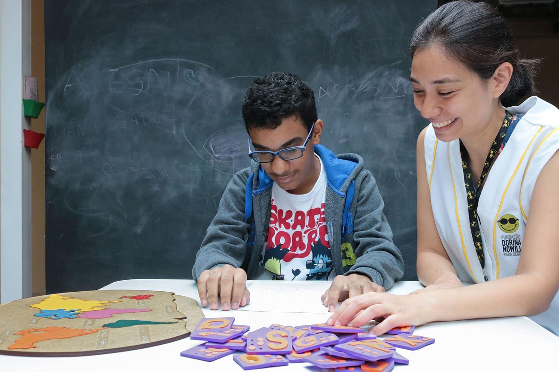 Aluno com baixa visão e professora em atividade educacional, ilustrando a pauta: Fundação Dorina inicia capacitação de professores neste sábado.