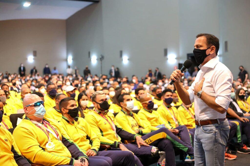 Foto do Governador de SP, em frente aos atletas paralímpicos, usando uniforme do Brasil, durante homenagem.