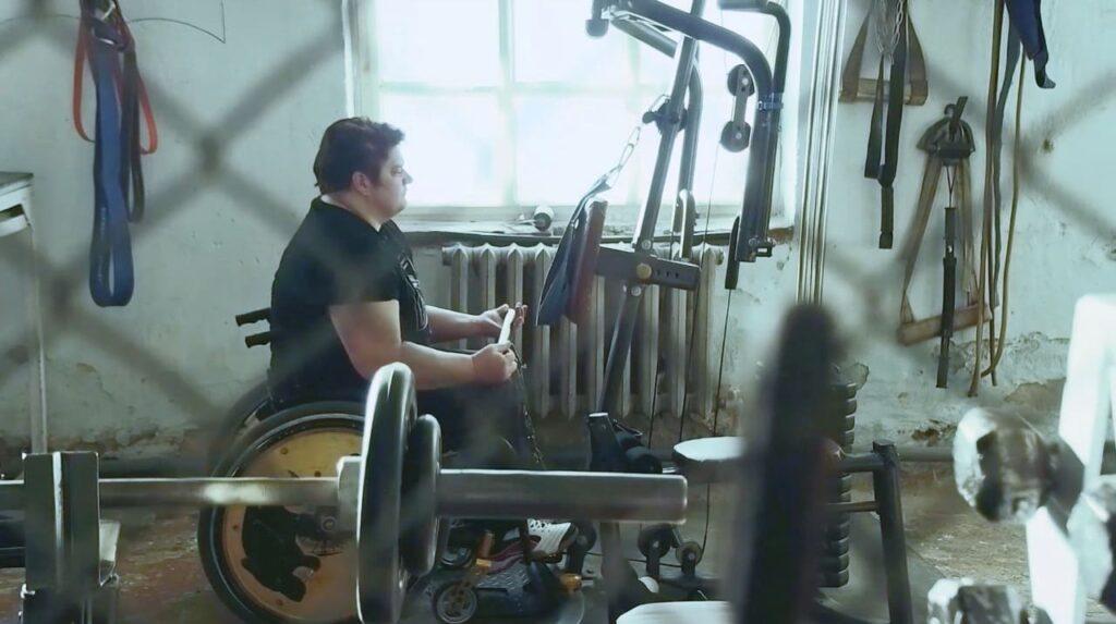 Imagem com mulher em cadeira de rodas se exercitando. A descrição detalhada está na legenda.
