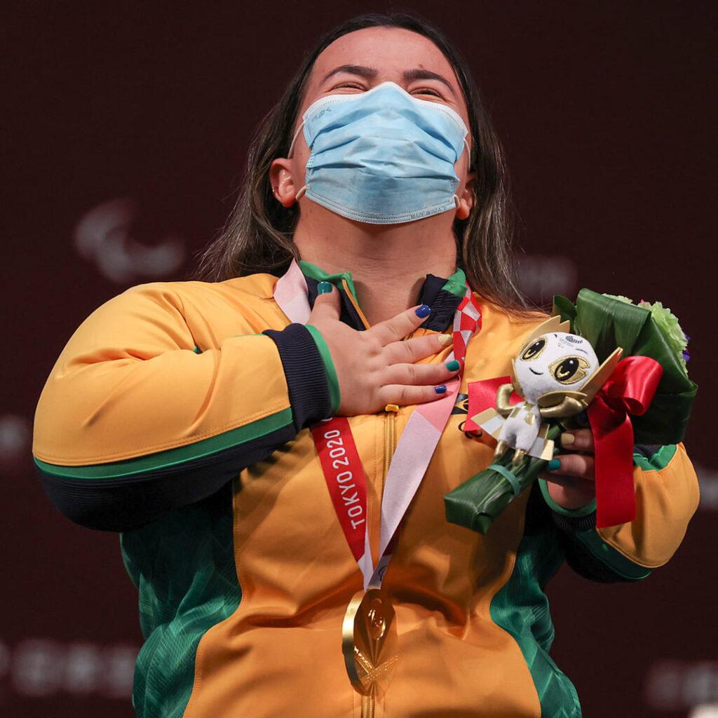 Ouro no halterofilismo em Tóquio 2020, Mariana D'Andrea, mulher com baixa estatura, cabelos longos castanhos e pele branca. Descrição detalhada na legenda.