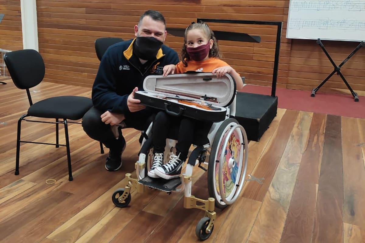 Pessoa adulta agachada ao lado de criança em cadeira de rodas, com violino no colo, mostrando a importância da música na vida de crianças com deficiência.