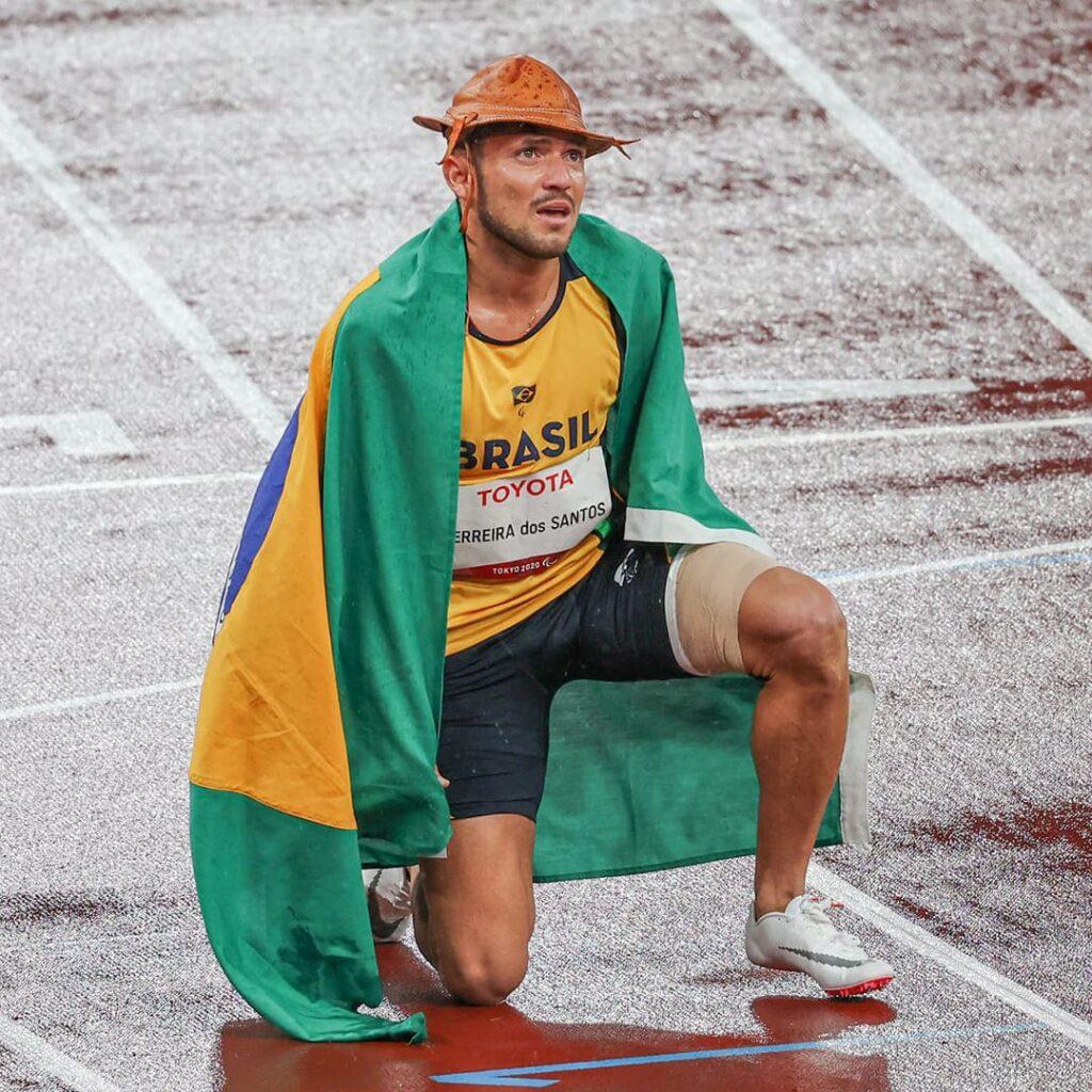 Fotografia do paraibano Petrúcio Ferreira, bicampeão paralímpico, ajoelhado na pista, com a bandeira verde e amarela nas costas e chapéu de couro do sertanejo.