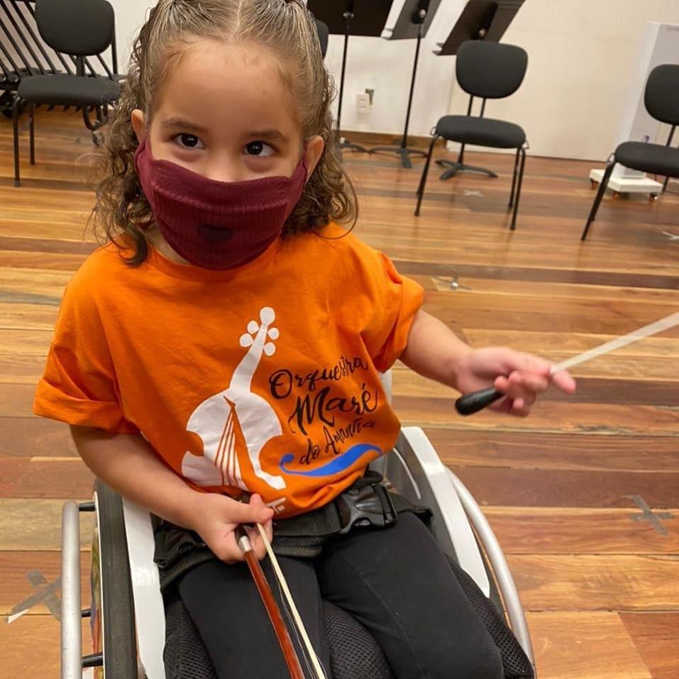 Criança branca de cabelos cacheados, sentada na cadeira de rodas, durante intervalo de ensaio da orquestra.