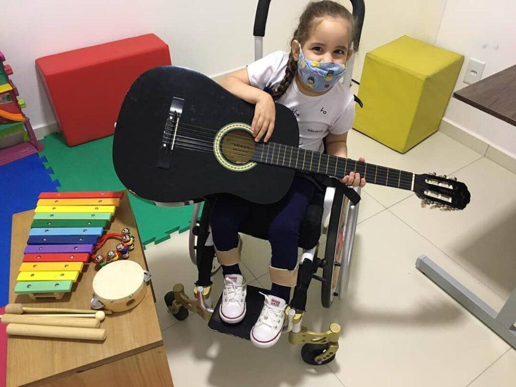 Criança de pele branca, com máscara hospitalar, está sentada em cadeira de rodas com um violão no colo.