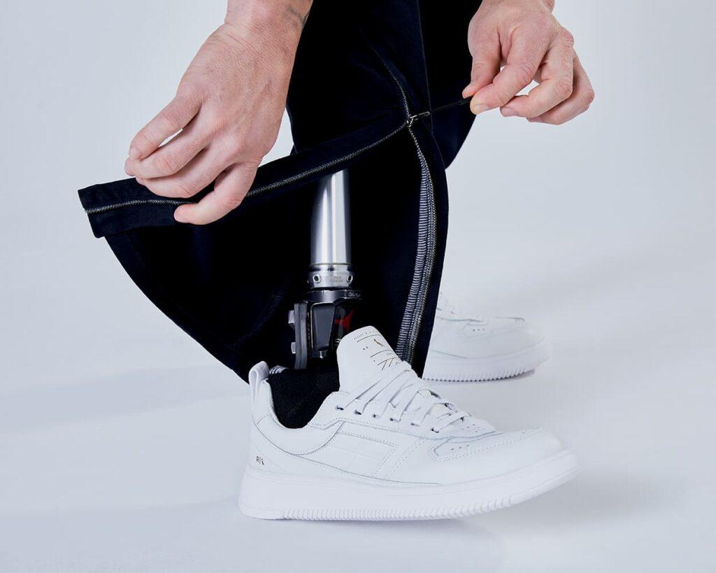 Modelo com prótese em membro inferior mostrando o zíper na barra da calça.