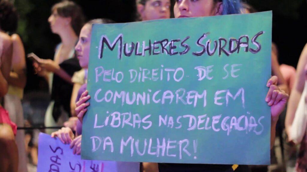 """Cartaz com texto descrito na legenda, cena do filme """"Seremos Ouvidas"""", que estreia em Nova edição do Assim Vivemos 2021."""