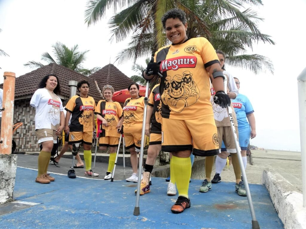 Fotografia da equipe feminina de futebol de amputados, com uniforme laranja. Descrição detalhada na legenda.