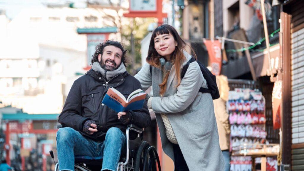 Homem em cadeira de rodas e uma mulher. Descrição detalhada na legenda, abaixo.