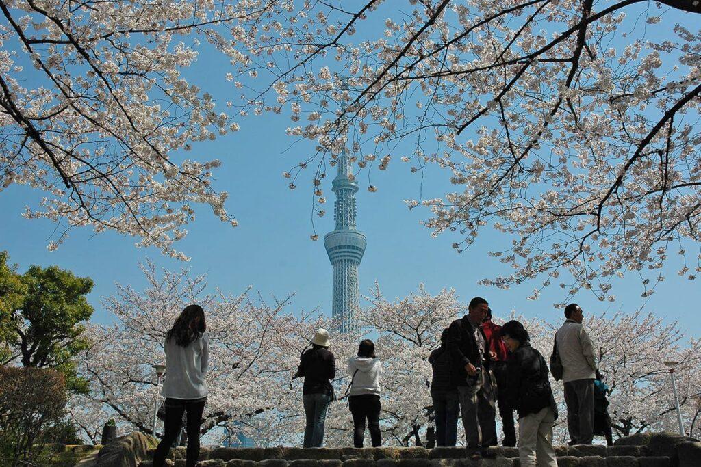 Fotografia em área externa, mostrando pessoas diversas e, ao fundo, a Tokyo Sky Tree.