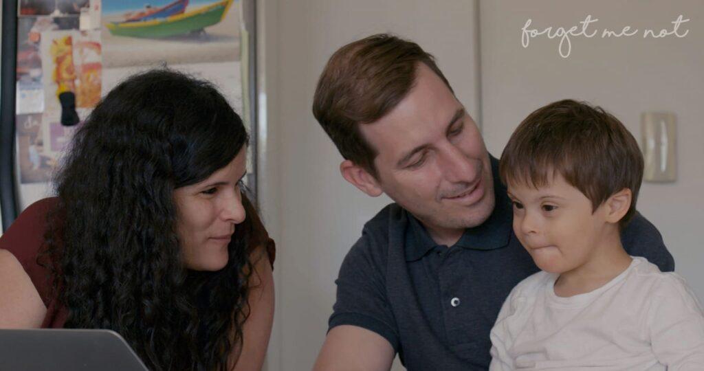Cena do documentário Um Lugar para Todo Mundo, com mãe, pai e criança com T21.