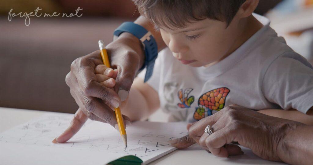 Cena do documentário Um Lugar Para Todo Mundo, com a mão de um adulto segurando a mão de criança com síndrome de Down e um lápis, escrevendo em um caderno.