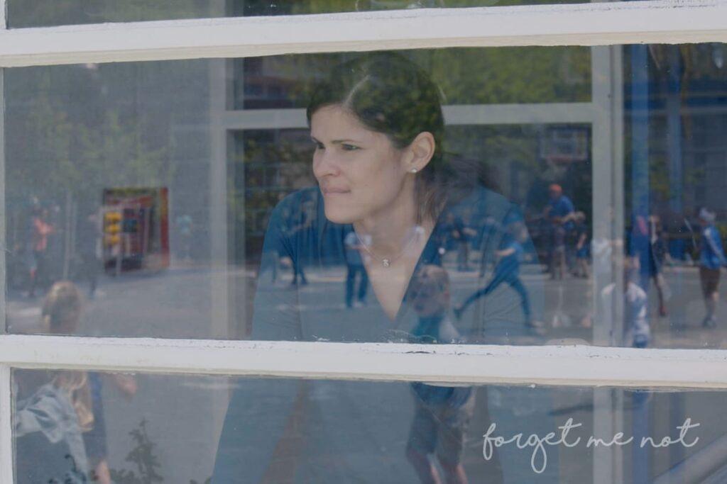 Hilda, mulher branca de cabelos pretos, está olhando pela janela.