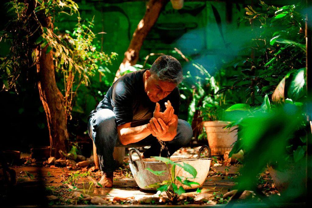 Homem lava as mãos na bacia, pelo Espetáculo Annata, do Núcleo Quimera de Criações (SP), Anatta Jardim.