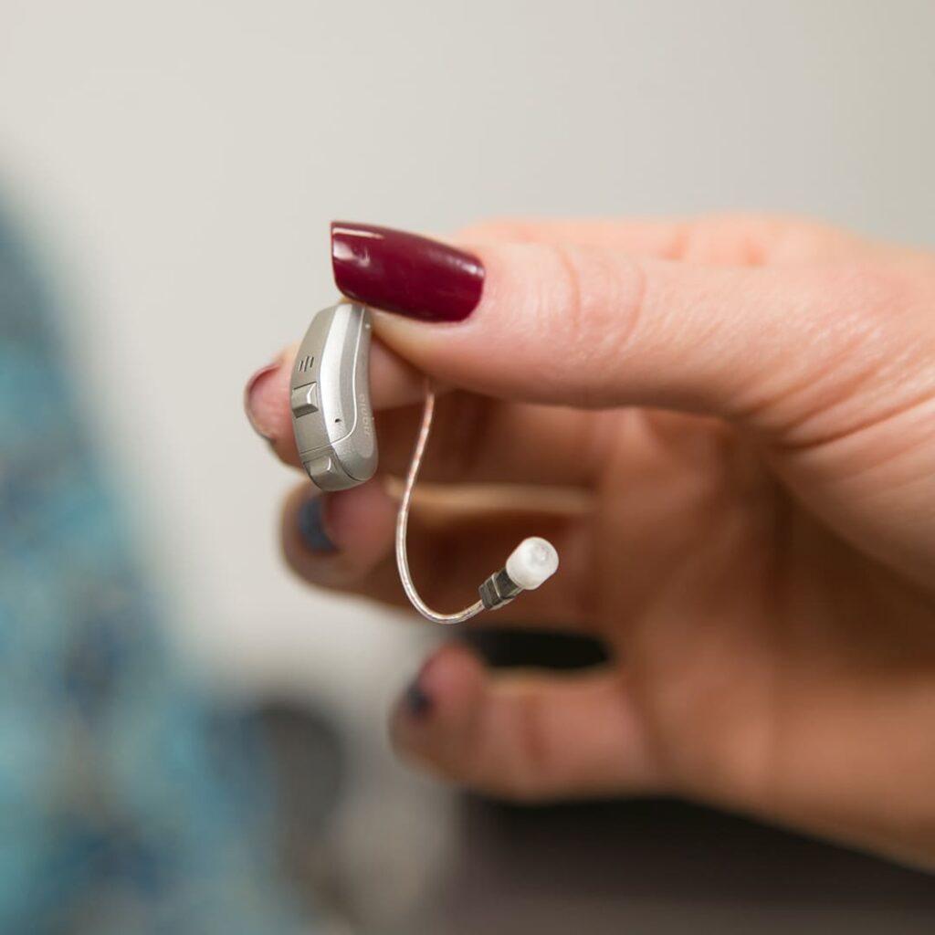 Mão branca com unhas compridas segurando aparelho auditivo infantil.
