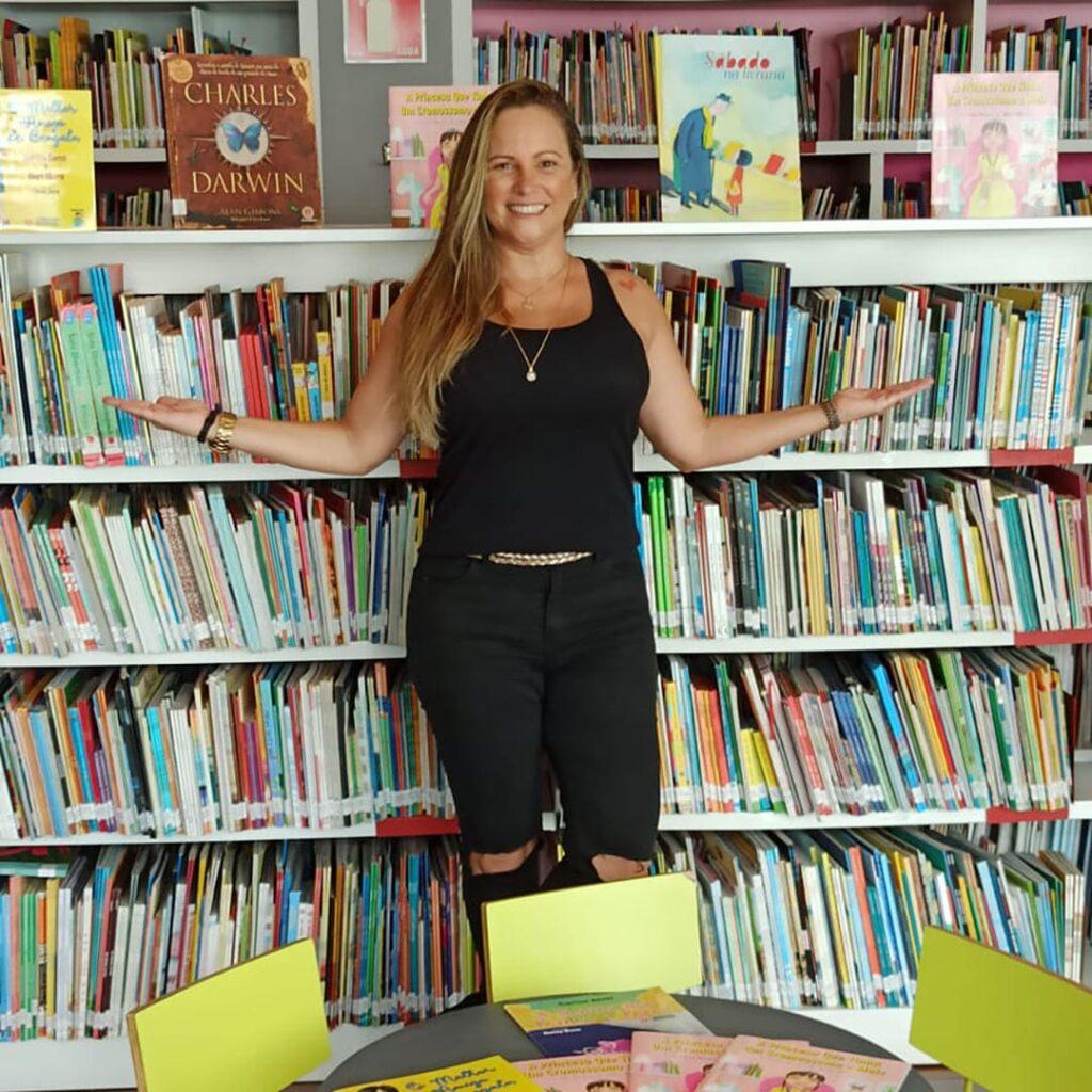 Carina, mulher branca com cabelos longos, em frente a estante de livros do projeto Literatura Acessível.