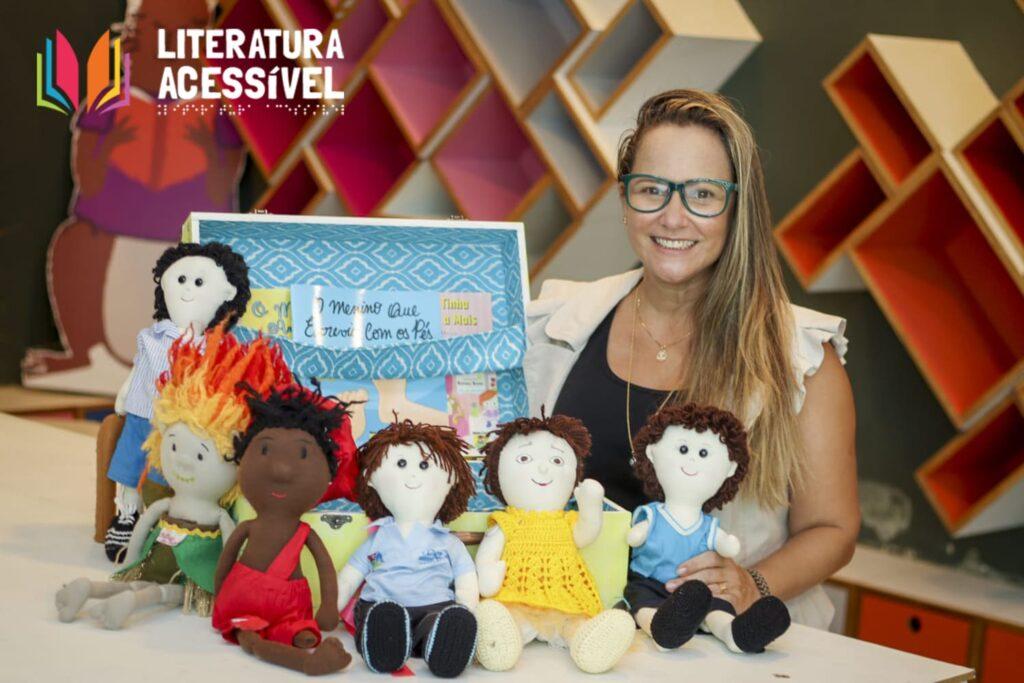 Foto da criadora do projeto Literatura Acessível, mulher branca e loira, com bonecos de pano e crochê.