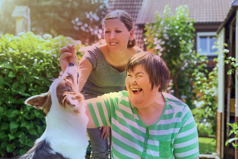 Mulher jovem e outra idosa, com deficiência intelectual, interagindo com um cão., pelo Dia Nacional do Idoso 2021.