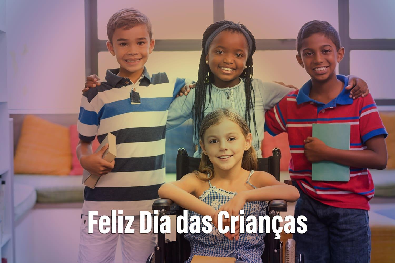 Quatro crianças sorrindo. Três estão em pé e uma é cadeirante, no Dia das Crianças 2021.