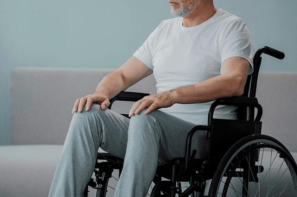 Homem idoso sentado em cadeira de rodas.