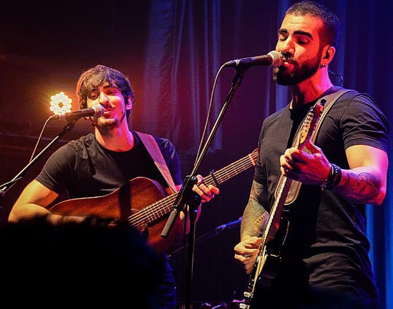Duo OutroEu, cantando no microfone e tocando violão.