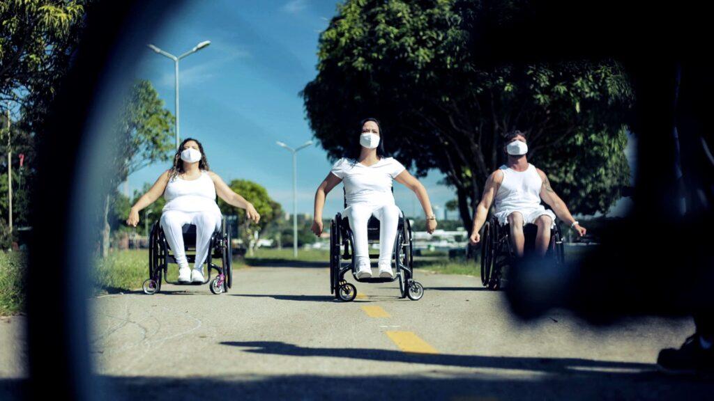 Foto com três artistas em cadeira de rodas, em área externa.